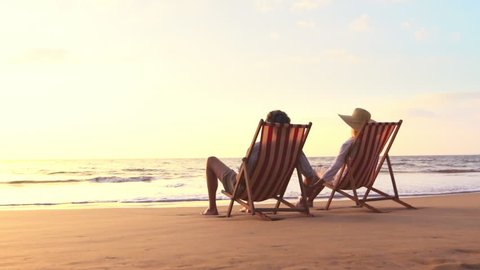 Retirement Vacation Concept, Happy Mature Retired Couple Enjoying Beautiful Sunset at the Beach. SLOW MOTION