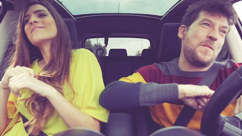 Beautiful woman with long hair and happy man dancing driving car happy