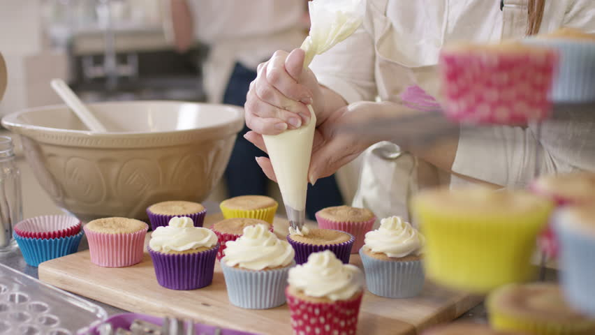 4K Woman with home bakery business piping cream onto cupcakes