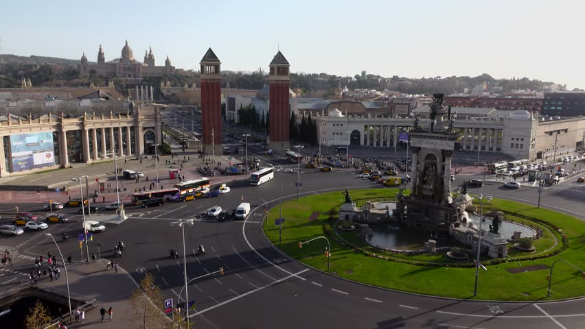Plaza de Espanya from above, famous Barcelona square, Venetian towers and Palau Nacional seen up to Montjuic hill side. Sparse traffic at roundabout, evening sun dim light and deep shadows.
