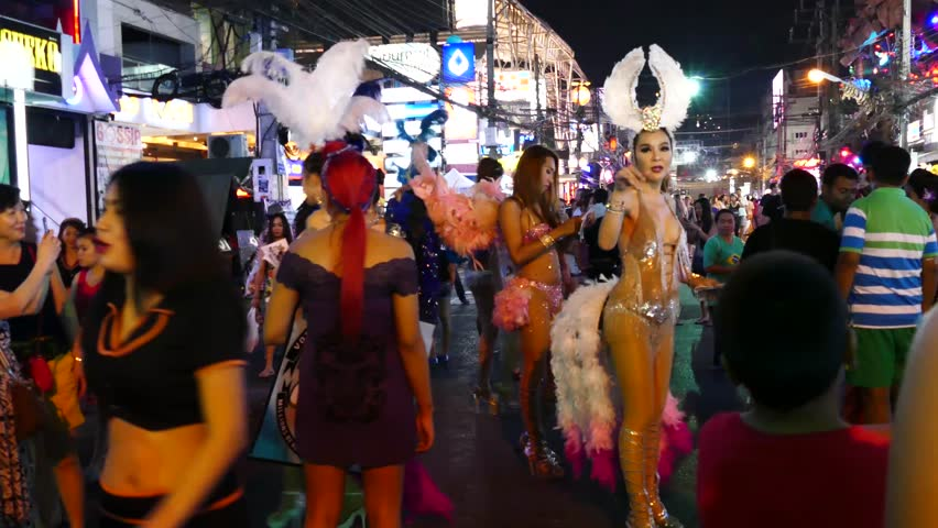 THAILAND, PHUKET ISLAND, PATONG 23. OCTOBER 2015;Ladyboys in garish costume standing on the Bangla Road and trying to collect customers for show.Tourists walking, night life, people traffic. 4K