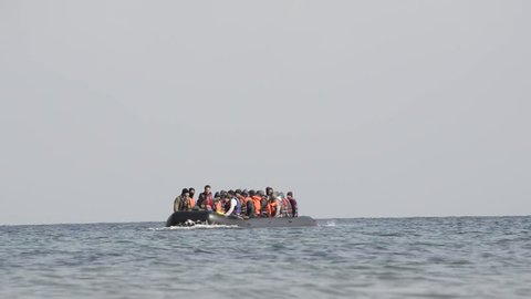 LESVOS, GREECE March 03, 2016: Refugees arriving in Greece in dinghy boat from Turkey. These Syrian, Afghanistan and African refugees land their boat at the coast of Lesvos near Mytilene.