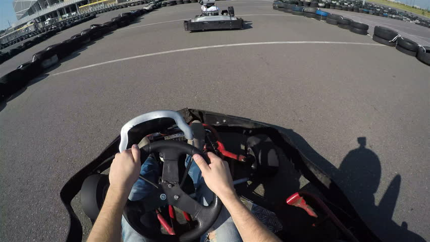 two drivers drive go kart and overtaking on outdoor track, camera is attached to the helmet, Man drives go kart on track, Karting filmed from the driver's view