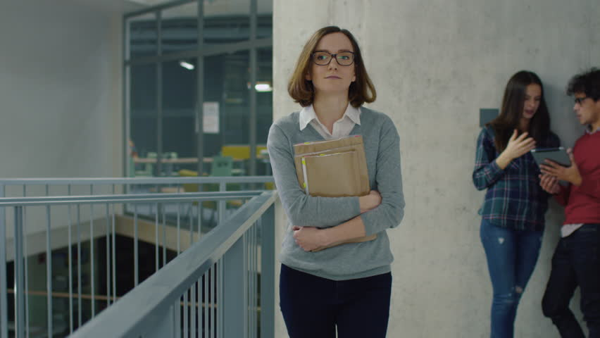 Portrait of a young student girl walking with books in an university hallway. Shot on RED Cinema Camera in 4K (UHD).