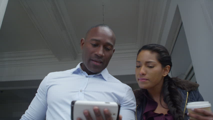4k Happy attractive ethnic couple using a smartphonet outdoors in the city | Shutterstock HD Video #15193168