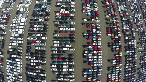 Aerial top down bird view of new car storage parking lot showing imported new vehicles or ready to export new automobiles storage facility car industry for American and European market for car sales