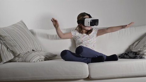 Girl wearing virtual reality goggles. Studio shot, white couch
