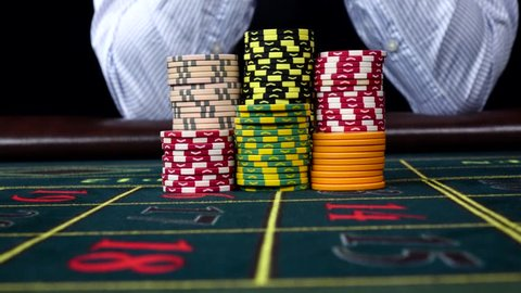 Croupier moves chips on table at casino, black, front view