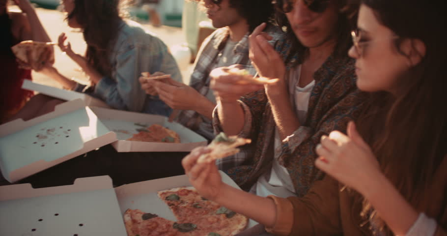 Cheerful hipster friends eating pizza sitting on the harbor close to their vintage van during a summertime road trip