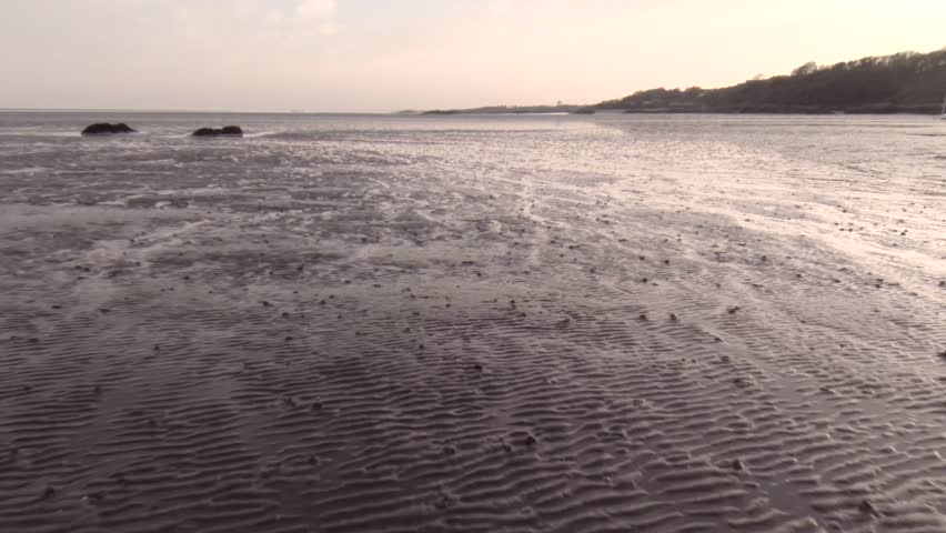 Aerial footage over a Scottish muddy beach at low tide during sunset.