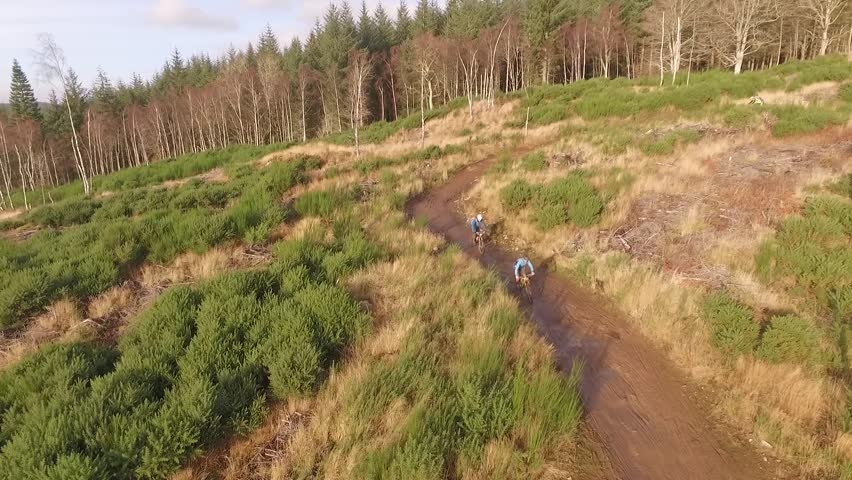Aerial mountain bikes Scottish hills autumnal colors low sun.