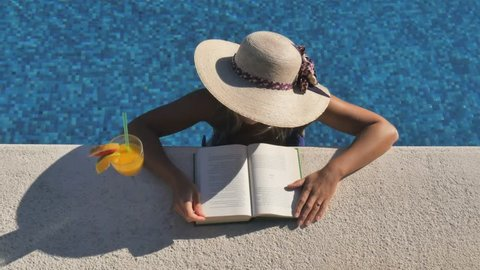 woman relaxing reading book in swimming pool top view