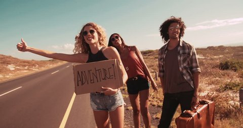 Hipster friends in the daytime stand on side of two lane highway hitchhiking while holding cardboard sign with the word Adventure written on it and sticking out thumb