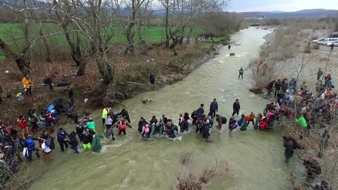 Idomeni, Greece - March 14, 2016: Hundreds of migrants and refugees cross a river, north of Idomeni, Greece, attempting to reach Macedonia on a route that would bypass the border fence