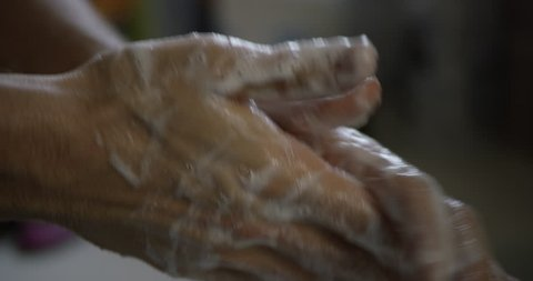 Close up of male lathering hands with soap before washing in bathroom sink, sanitation and personal hygiene