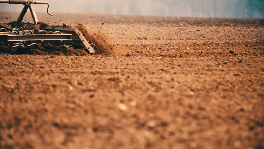 Tractor cultivating land in extreme close up slow motion. | Shutterstock HD Video #15300748
