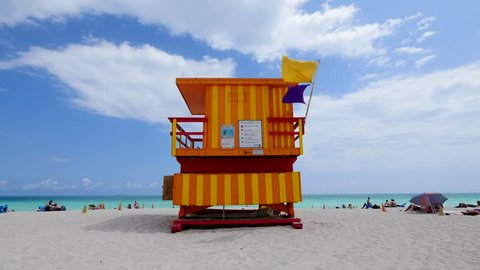 Lifeguard tower in a typical colorful Art Deco style on a bright sunny summer day, with blue sky and Atlantic Ocean in the background. World famous travel location. Miami beach, Florida.