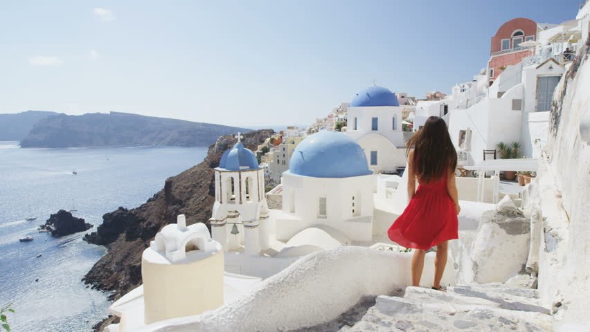Elegant woman walking down stairs in Oia Santorini. Female tourist is in red dress on sunny day. She is visiting the famous tourist attraction destination on Europe travel. RED EPIC SLOW MOTION. | Shutterstock HD Video #15325060