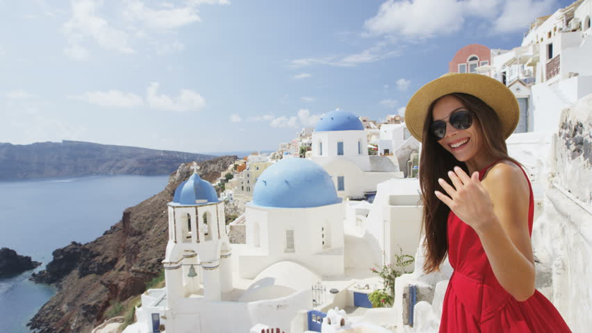Woman welcome you to walk with her on Santorini. Female tourist is enjoying summer vacation travel showing welcoming gesture smiling happy. Traditional typical Oia village, Santorini, Greece, Europe. | Shutterstock HD Video #15325069