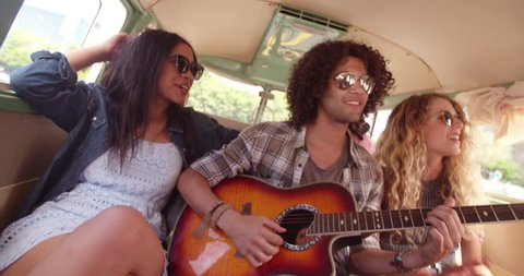 Two Multi Racial Hipsters, one girl and one man, playing guitar and singing together in the back of a van