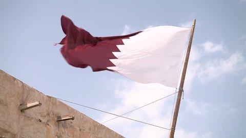 Qatari flag waves in the Souq Waqif standing market in Doha, Qatar