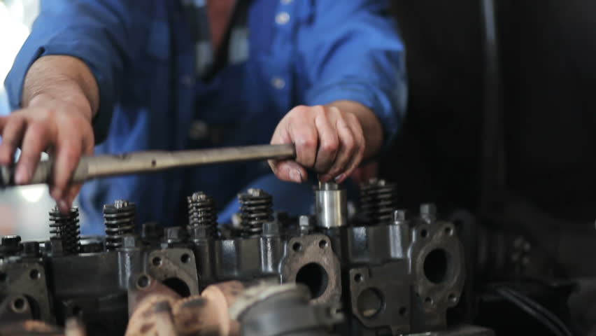 Worker repairing the engine of the truck to the service centre. Close up of technician indoors. Human with dirty hands soiled in machine oil | Shutterstock HD Video #15339010