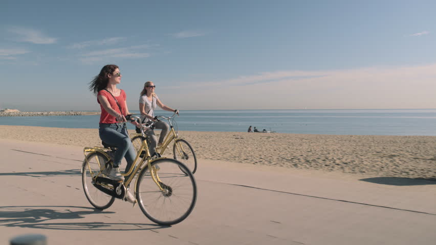 Young Adult Tourists cycling on beach in summer