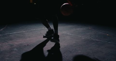 Male urban basketball player dribbles ball in crouched position in an inner-city basketball court lit by single street light