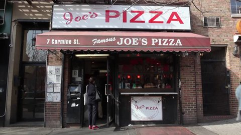 New York, New York, USA -  March 16, 2016: Joe's Pizza on Carmine Street in Greenwich Village New York City. This is a small but well known pizza establishment. People can be seen.