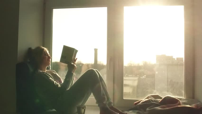 beautiful young woman sitting on window sill with coffee end reading book on background of sunset