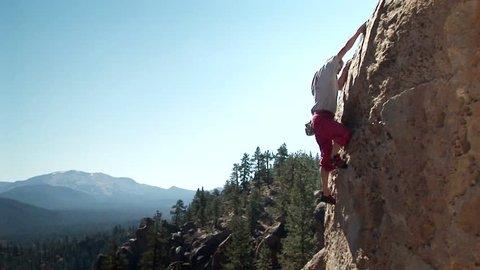JOSHUA TREE, CA - CIRCA 2009: A man climbs up the side of a mountain circa 2009 in Joshua Tree.