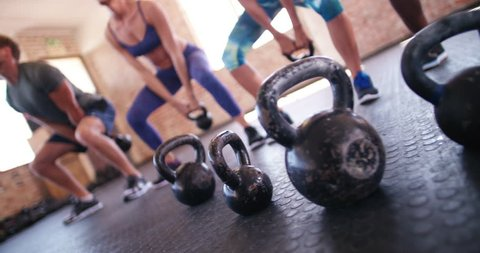 focus on Kettlebells on crossfit training. group of young adult athletes doing kettlebell exercise during a crossfit workout at the gym