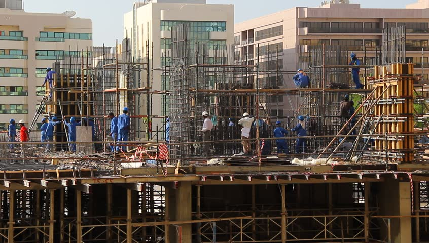 DUBAI, UNITED ARAB EMIRATES - OCTOBER 26, 2013: Unidentified builders at work, create reinforced steel cage for building skeleton, erect internal walls, put falsework. Medium telephoto shot, real time