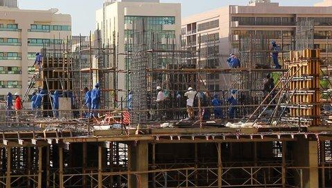 DUBAI, UNITED ARAB EMIRATES - OCTOBER 26, 2013: Unidentified builders at work, create reinforced steel cage for building skeleton, erect internal walls, put falsework. Medium telephoto shot, real time