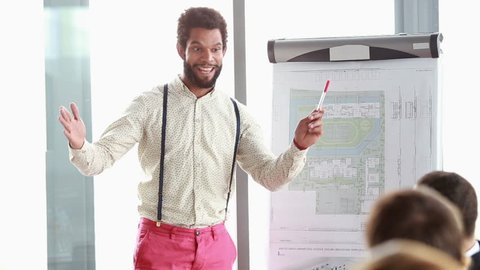 Handsome young man pointing at flipchart while giving presentation to his colleagues
