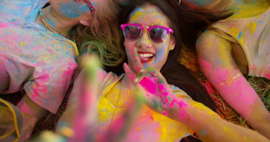 Multi-Ethnic group covered in Holi powder lay in grass laughing and looking up and gesturing peace sign to the camera in a park at a Holi festival in the summer - 4K stock footage clip