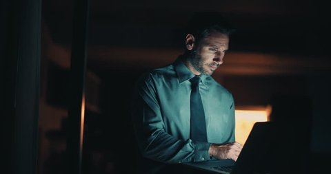 Serious man in blue shirt and blue tie working on laptop at night time in office