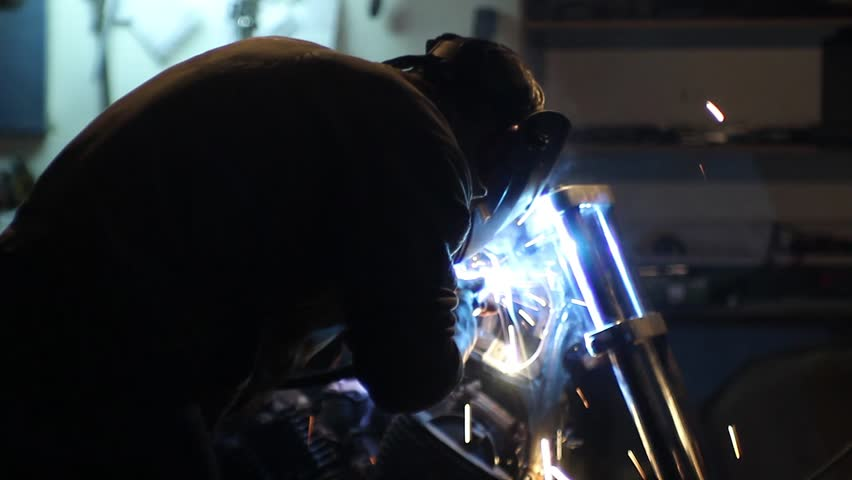 Automaster weld the frame of a custom motorcycle in the garage. Sparks welding machine. Protective face mask. | Shutterstock HD Video #15430030