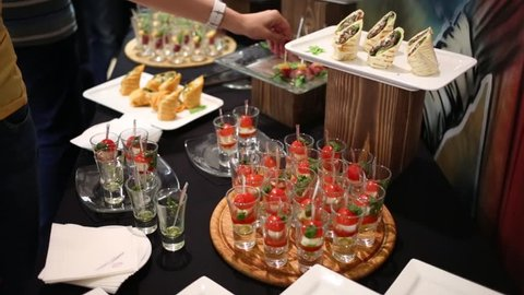 Canapes cold dishes and hands of people taking food