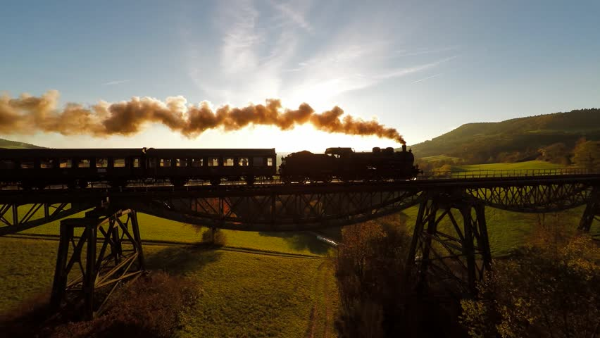 Nostalgic steam engine locomotive crossing bridge at sunset. old historical train technology background
