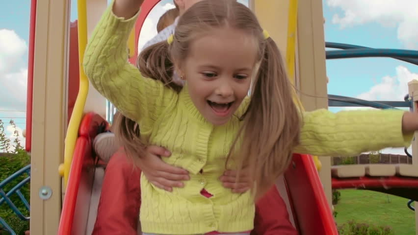 b55bbd3fe6863 Two boys and cute girl having great fun while riding down slide in the  playground