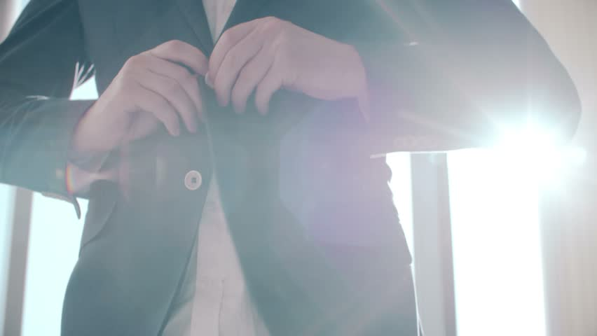 Buttoning a jacket. Stylish man in a suit fastening buttons on his jacket preparing to go out.
