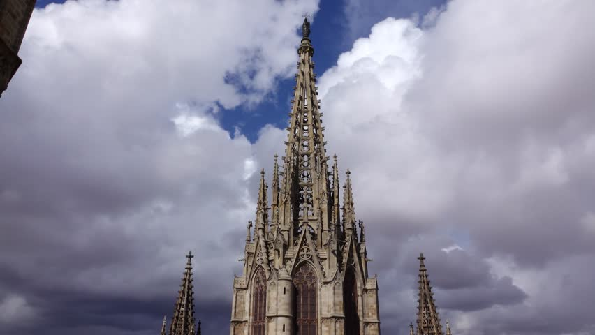 POV camera move at top of Ghotic church, show openwork spiked spire against cloudy sky. Barcelona Cathedral details, rooftop observation deck, low angle shot of main facade pointed tower from back.