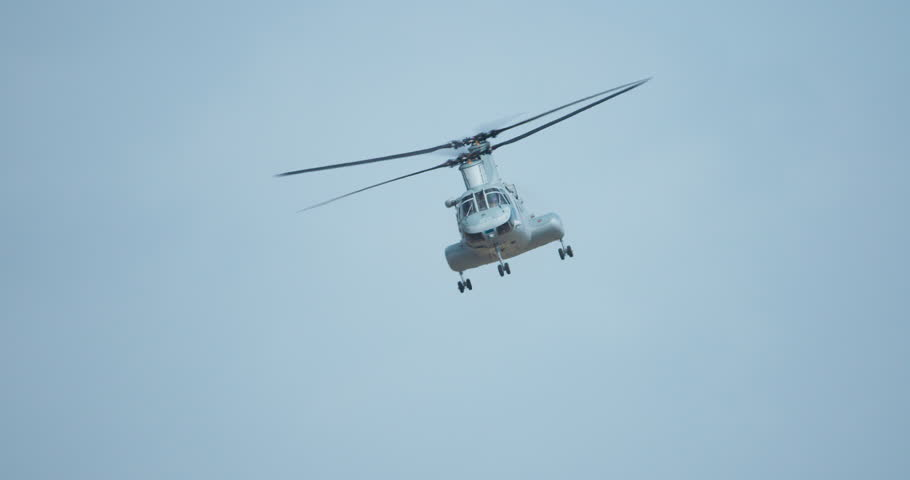 Chinook CH-47 tandem rotor military helicopter flying against blue sky.  No legible markings.  4K.