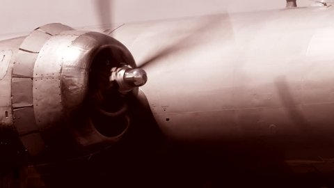 WW II airplane bomber engine and propeller spinning close-up in B&W.
