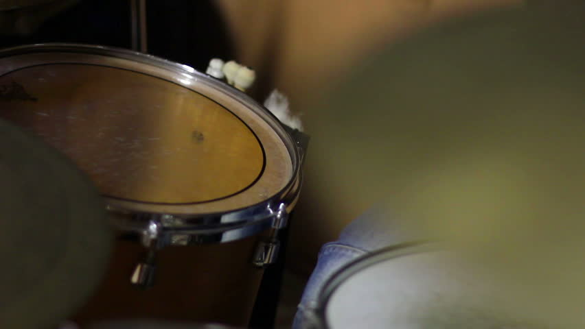 Drummer playing at drums set in a studio