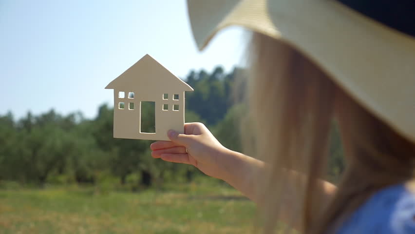 Slow motion of a woman in summer hat holding wooden house model on the background of green forest and blue sky. Concept of eco or country house, real estate and mortgage