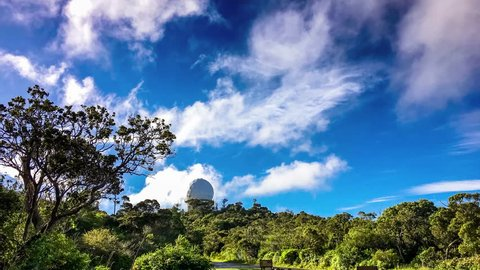 Bright white clouds drift over a tropical rain forest landscape and blue  sky, with slow zoom toward radar dome / observatory in kokee state park on  kauai hawaii, viewed from near kalalau lookout point