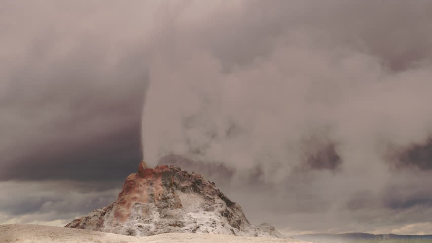 White Dome Geyser erupting with dramatic sky and clouds.  Yellowstone National Park, Wyoming and Montana, USA. 4K.