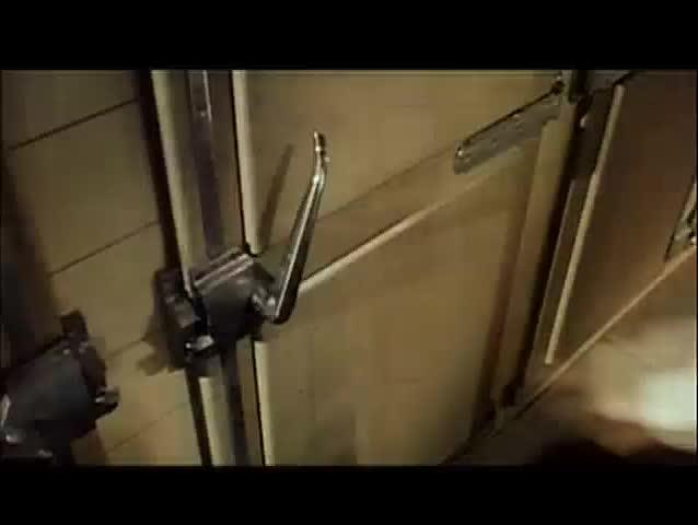 Worker pulling open mortuary refrigerator door, 1960s